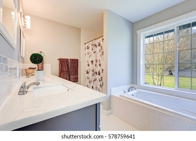 Light filled bathroom interior accented with double sink blue vanity cabinet topped with marble counter top and white jetted tub positioned by the window. Northwest, USA