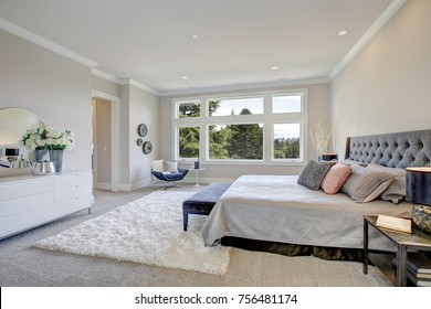 Light filled bedroom boasts a king size bed with tufted headboard dressed in grey bedding facing large white dresser topped with a round mirror. Northwest, USA