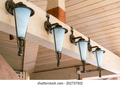 Light fittings in the house interior. Retro lamps on a wooden cladding at home or summerhouse. Vintage lantern indoor in daylight.