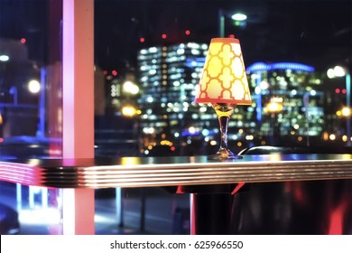 A light fixture sitting on a table at a high end club. With the nigh time Boston urban skyline in the background.
