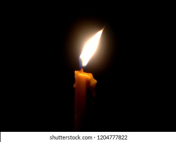 The light from the flame of the candle shines in the dark. Light from candles.
