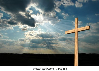 Light form the sky shining down on a wooden cross