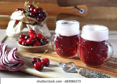 Light fruit craft beer and cherry on wooden chopping board, rustic style