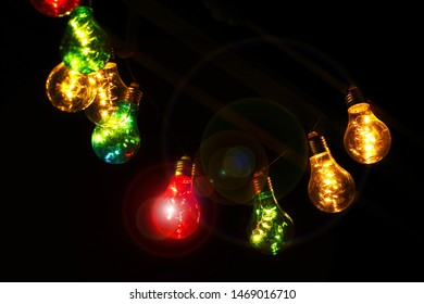 Light garland Colored bulbs at night background Summer warm welcome atmosphere