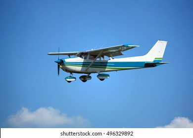 Light general aviation cessna aircraft on final with cloud sky landing configuration