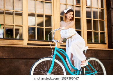 Light girl in an airy white summer dress on a blue vintage bike on a wall background with big windows