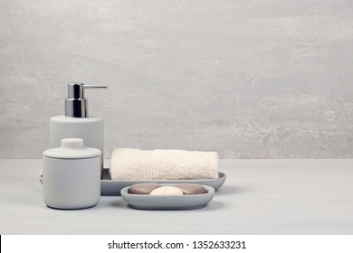 Light gray ceramic acessories for bath - bowl, soap dispenser and other accessories for personal hygiene. Decor for bathroom interior