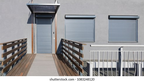 Light gray metal blinds on the doors and windows of the house