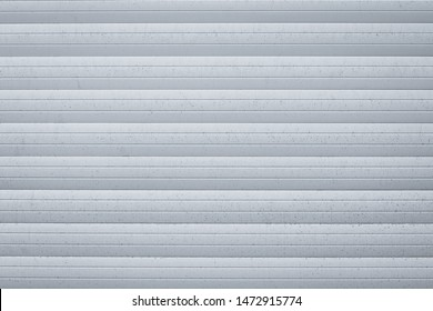 Light gray metallic jalousie. Texture of corrugated metal striped surface. Dirty ribbed background with straight lines. Copy space. Exterior element.