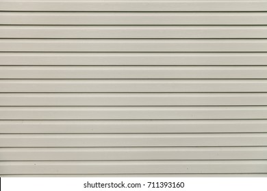 Light gray (white) vinyl wooden siding panel background with imitation wood texture.