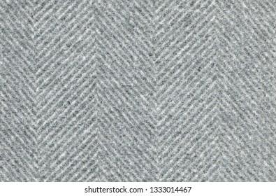 Light gray woolen fabric striped zigzag. Herringbone tweed, Wool Background Texture. Coat close-up. Expensive men's suit fabric. Virgin wool extra-fine. High resolution.