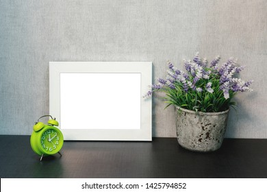 light green alarm clock, empty white wooden photo frame and decorative flower in a flowerpot on the shelf in the living room at home, the concept of a modern interior and lifestyle, mock-up