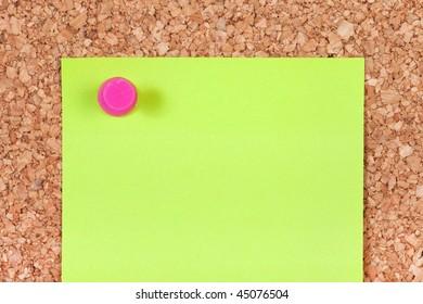Light green blank note on the corkboard.