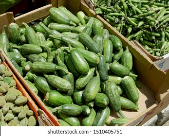 Light green fresh zucchini in a cardboard box in the market, next to raw beans.