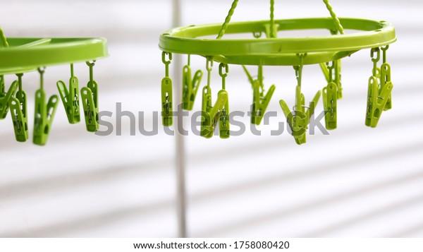 薄緑色のプラスチック製の洗濯ばさみ、ハンガーの上の緑色のクリップの衣類、洗濯後の衣類や下着に使用。 白い亜鉛ぼかしの背景にタイの便利なオブジェクトスタイル。