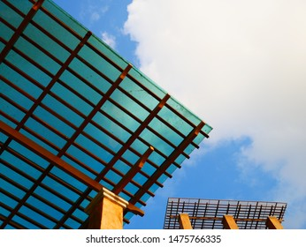 Light green polycarbonate sheet with wooden structure roof on orange plaster pillar. Nice wooden roof structure with transparent sheet make we safe from rain but still can get lighting and see the sky