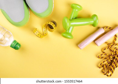 Light green sports sneakers, bottle water, jump rope, bright little weights and a colorful centimeter on a yellow background with place for text