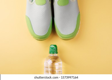Light green sports sneakers and bottle of water on a yellow background with place for text