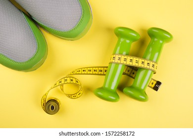 Light green sports sneakers, bright little weights and a colorful centimeter on a yellow background with place for text