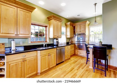 Light green tone kitchen with wooden cabinets and small table with chairs.