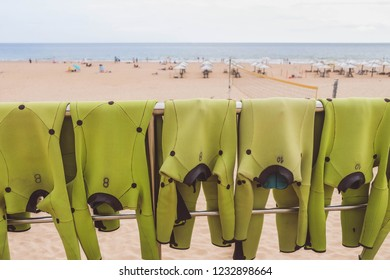 Light green wetsuits is drying out in sun for next group surfing lesson on ocean with sandy beach and seascape on background