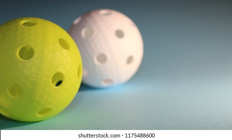 Light green and white floorball balls on blue background with copy space.