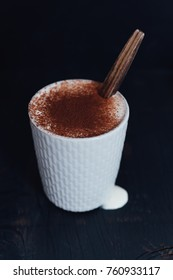 Light grey stoneware mug with stitched pattern filled with hot chocolate with slightly whipped cream and dusted with cocoa powder on black background and wooden spoon