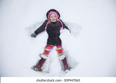 Light hair girl in pink hat play with snow, make snow angel.