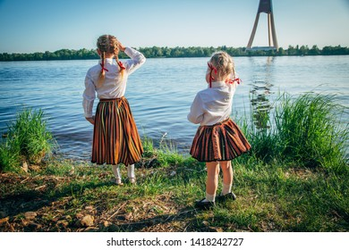 Light hair girls in Latvian traditional clothing posing on nature background. Preparing Ligo festival. Riga. Latvia