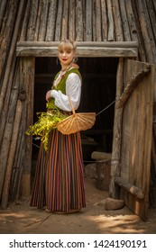 Light hair young lady in Latvian traditional clothing posing on nature background in village. Preparing Ligo festival. Riga. Latvia