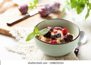 Light healthy dietary breakfast: couscous with berries in blue bowl close up