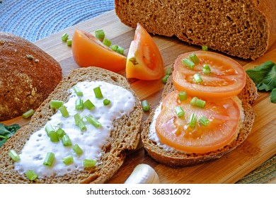 Light, healthy and fresh tomato, yogurt, dark bread meal with chopped parsley in portrait side crop
