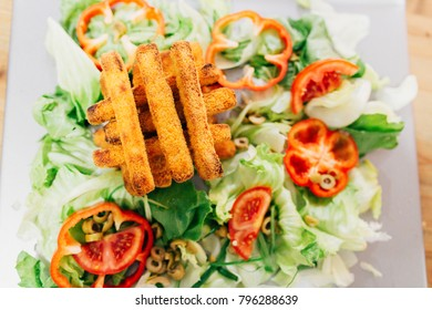 A light, healthy and vegetarian meal with lettuce, peppers and cheese nuggets.