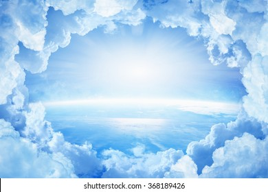 Light from heaven, blue planet Earth in white clouds, bright sunlight from above. Elements of this image furnished by NASA nasa.gov - Shutterstock ID 368189426