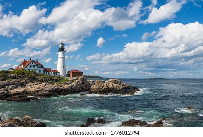 Light house on a rocky sea coast with blue sky backdrop with clouds