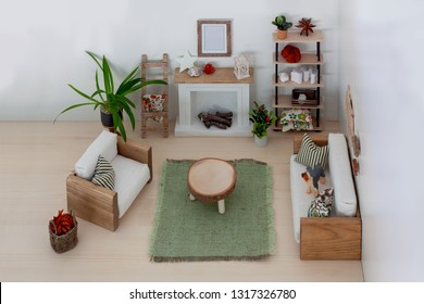 Light interior of a dollhouse living room furnished with wooden handmade furniture, Loft style sofa and armchair with white upholstery, fireplace, bookshelf, wood slab coffee table, High angle view