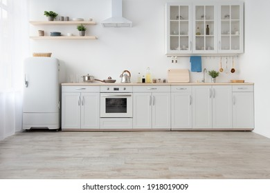 Light kitchen in daylight, simply, minimalist scandinavian interior. White furniture, small refrigerator, stove with utensils, extractor hood, shelves with plants in pots, curtains in morning