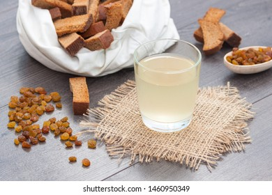Light kvass in glass with rye bread and raisins on wooden background