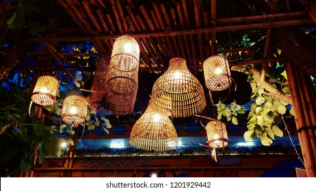 Light from lamp inside the Wicker bamboo trap hanging on the tree for house interior decoration style village or country side of Thailand, This wicker use to be for catch or keep fish in the river.