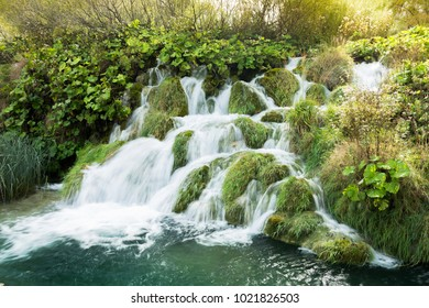Light leak from the sun over a small waterfall in Plitvice Lakes national Park. The water is flowing in different directions and it passes the lush green grasses. The water is turquoise.