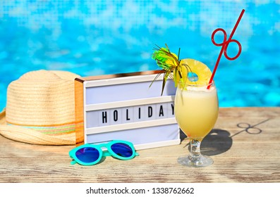 Light letterbox, hat, sunglasses and pinacolada cocktail with decor on the pool background