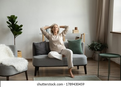 In light living room on modern comfy couch rest aged woman, grandma closed eyes enjoy peace and placidity, put hands behind head breath fresh humidifier air. No stress, carefree retired life concept - Shutterstock ID 1789430459