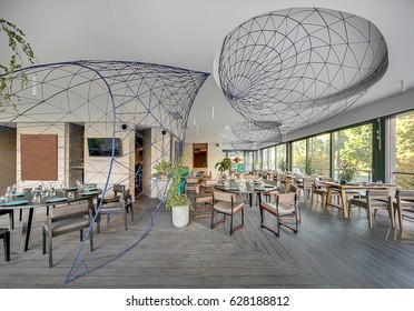 Light modern cafe with large windows and a parquet on the floor. There are many tables with glasses and plates,  chairs, sofas, plants in the concrete pots, several metal reticulated constructions.