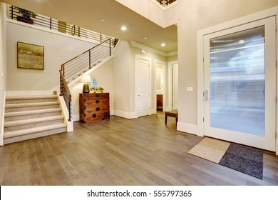 Light modern foyer design boasts vintage steamer trunk dresser next to staircase with metal horizontal railings, glossy entrance door and dark hardwood floors. Northwest, USA