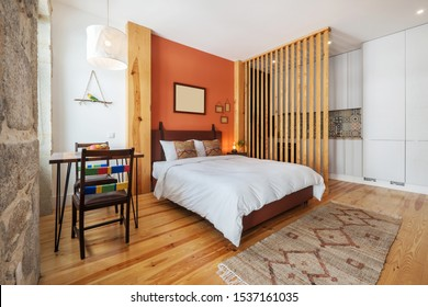 Light modern interior design, studio apartment with kitchen, double bed, big windows and wooden decor. Orange and white color wall