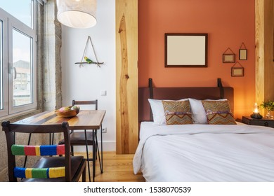 Light modern interior design, studio apartment with double bed, big windows and wooden decor. Orange and white color wall