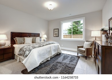 Light modern master bedroom interior with darkwood bed and dresser