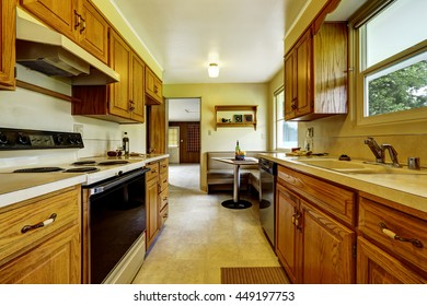 Light narrow kitchen room with corner sofa, small table, wooden cabinets and tile floor