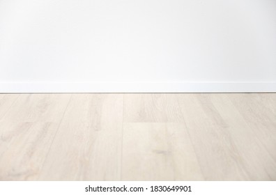 light oak laminate with white baseboard and white wall as background for design concepts