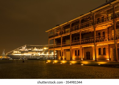 Light up old brick building in front of cruise ship in Yokohama at night